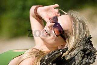 Blond woman in bikini sunbathe on beach