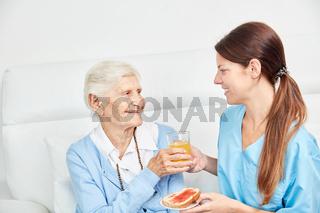 Pflegedienst Frau bringt Seniorin einen Saft