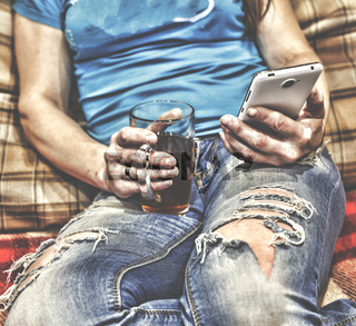 Young woman in torn jeans is using a white smartphone while sitting on the couch