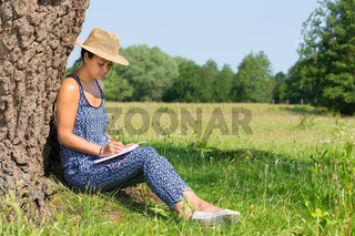 Woman sitting against tree writing in nature
