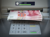 ATM machine and money. Withdrawing yuan banknotes.