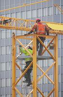 Bauarbeiter auf einem Kran