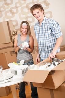 Moving house: Young couple unpacking kitchen dishes