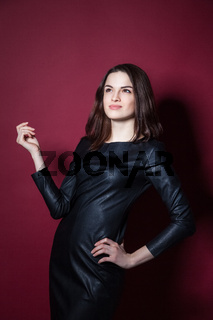 Portrait of young beautiful woman in leather dress on red background