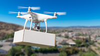 Unmanned Aircraft System (UAS) Quadcopter Drone Carrying Blank Package Over Neighborhood.