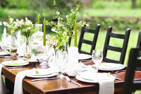 Decoration of wedding table with crystal vases, flowers and branches