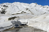 Passtrasse zwischen hohen Schneemauern über den Gotthardpass, Schweiz