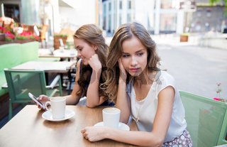 young women with smartphone and coffee at cafe