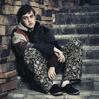 Sad young fashion hipster man sitting on the steps