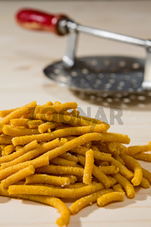 Closeup of Passatelli original Italian pasta over a wooden background