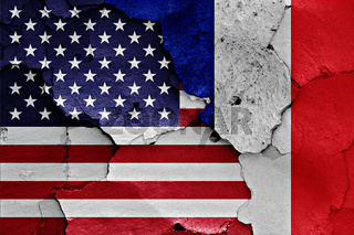 flags of USA and France painted on cracked wall