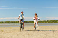 happy young couple riding bicycles at seaside