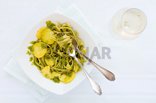 Linguine pasta with pesto genovese, potatoes and white wine glass