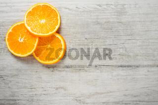 Slices of fresh oranges on white wood background