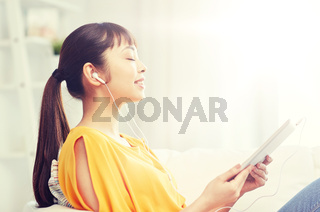 happy asian woman with tablet pc and earphones