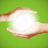 Zwei Hände halten eine leuchtende Sonne