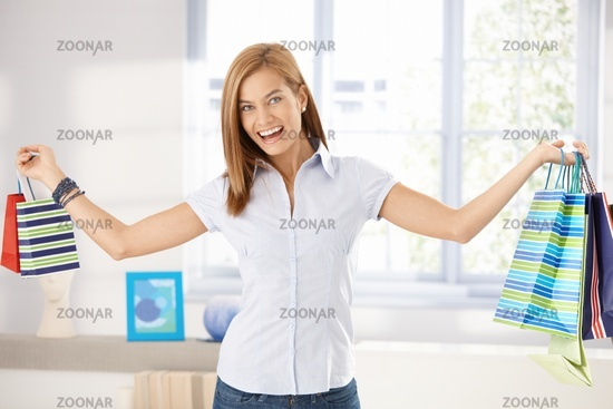 Happy woman arms wide open holding shopping bags