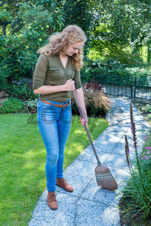 Young dutch woman sweeps garden path with wicker broom