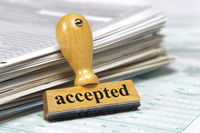 accepted printed on rubber stamp laying on documents