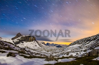 Starry night sky in snowy alpine mountains. Winter in Swiss Alps, Switzerland.