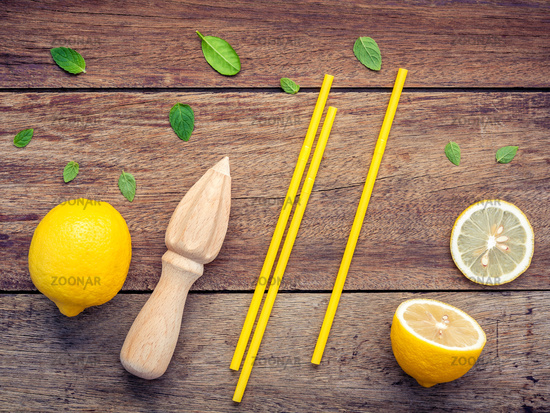 Fresh lemon and wooden juicer for summer juice and cocktail. Fresh lemon sliced ,yellow straw and peppermint leaves set up on shabby wooden background flat lay.