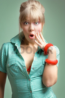 young surprised blonde posing over green background