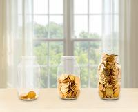 Three glass jars of growing savings on shelf
