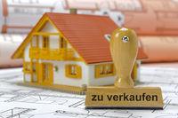 Modellhaus auf Bauplan mit Holzstempel