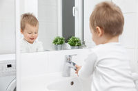 Cute toddler in the bathroom mirror learning how to wash his face