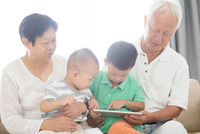Grandparents and grandchildren using tablet pc