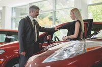 Auto showroom, young woman choosing car talking to dealer.