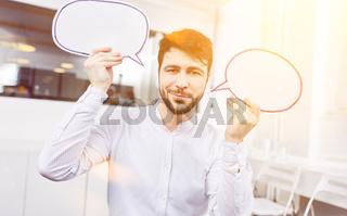 Business Mann hält Sprechblasen als Zeichen für Dialog