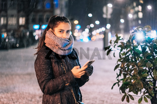 Stylish woman holding phone in city street