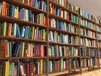 Library stacks of books and bookshelf.