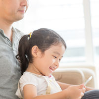 Father and child using digital tablet.