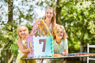 Mutter und Kinder freuen sich über Traumhaus Puzzle