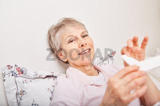 Seniorin nimmt Arznei aus Medikamentenbox