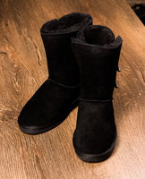 Top view of winter boots standing on wooden background.