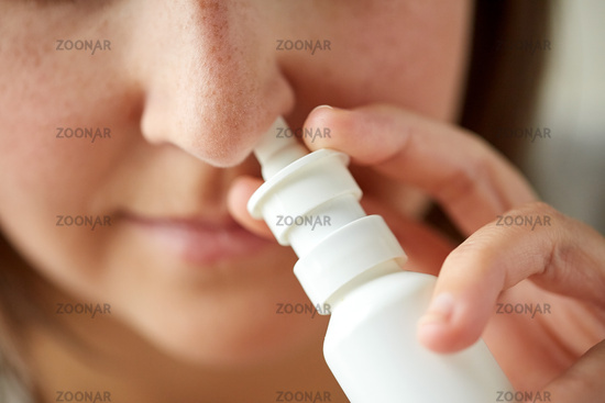 close up of sick woman using nasal spray