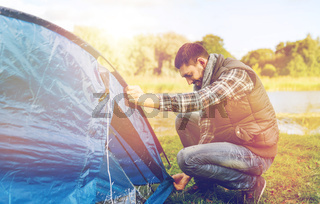 happy male traveler setting tent up outdoors