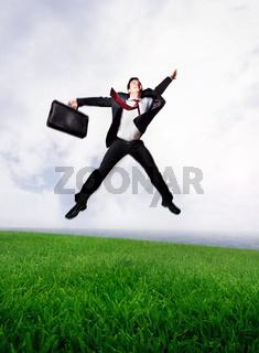 Jumping business man on Green Field