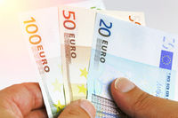 Hands counting euro money bills on white background