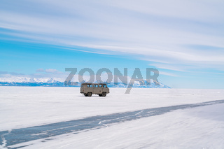 Grey car parks on snowy surface of Frozen Lake Baikal