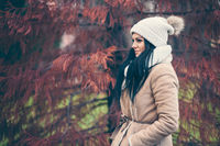 Outdoor portrait of a young woman wearing a coat and hat