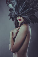 Party, Nude brunette woman in a headdress made of big feathers in sensual and mysterious poses