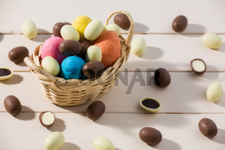 Easter chocolate eggs in a small basket over a table