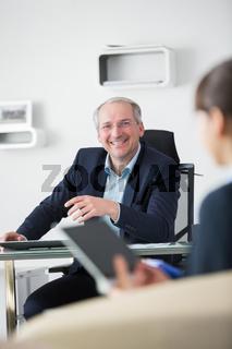 Älterer Geschäftsmann lacht über einen Witz