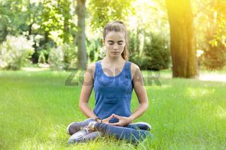 meditating teenage girl in a park
