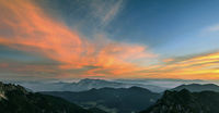 Mountain landscape at sunset in Julian Alps. Amazing view on colorful clouds and layered mountains.