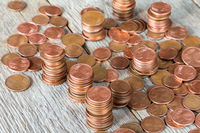 Euro cents stacked on wooden background.